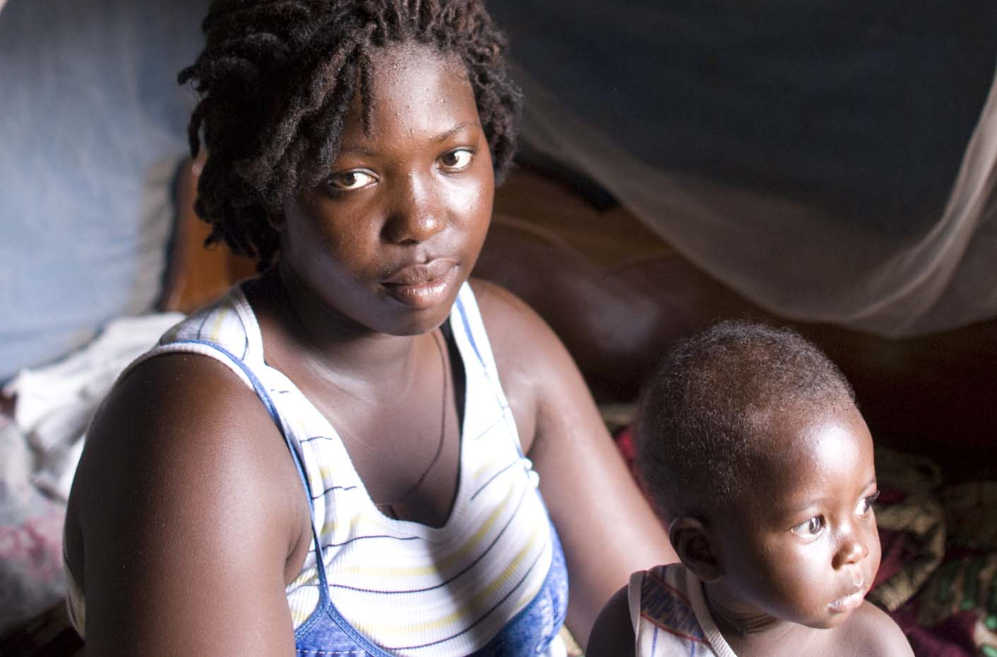 A woman sitting with her child beneath a mosquito nets, Ghana. Part of an exhibition of photographs from the Pfizer MAM project shown at the conference.